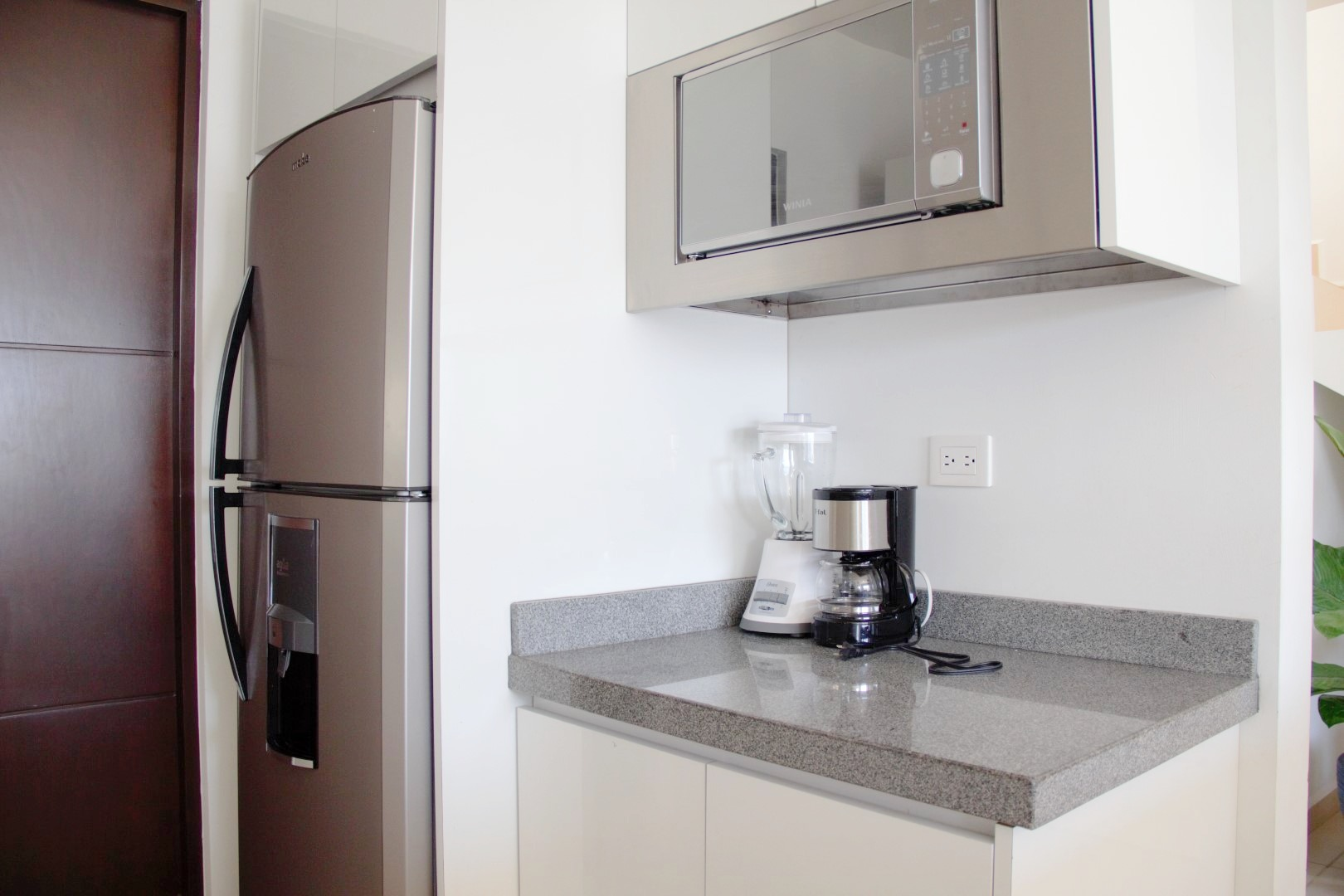 Kitchen with refrigerator, coffee maker and blender, and mounted microwave.