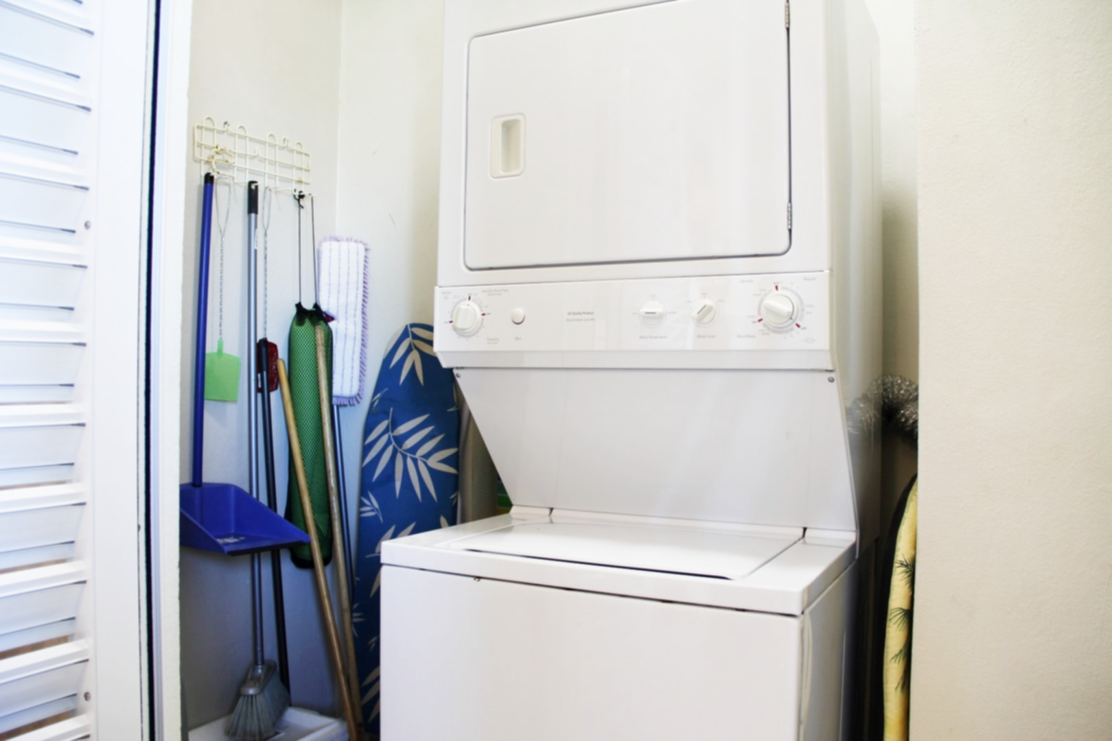 Full-sized washer and dryer in cleaning closet.