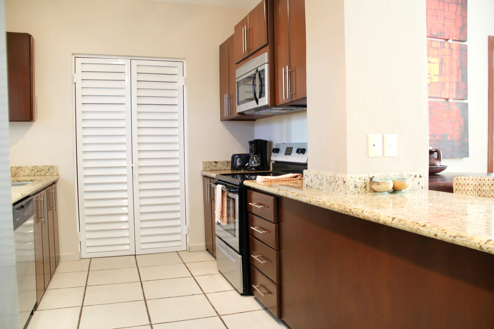 Galley style kitchen with cleaning closet at the end.