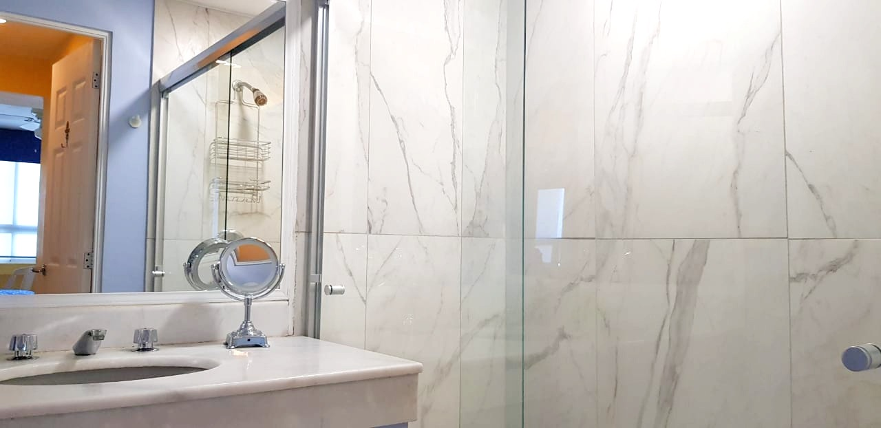 Updated master bathroom with new tiled shower and glass doors.