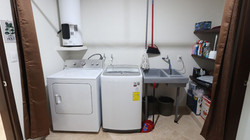 Service area with full size washer, dryer, wash sink and storage.