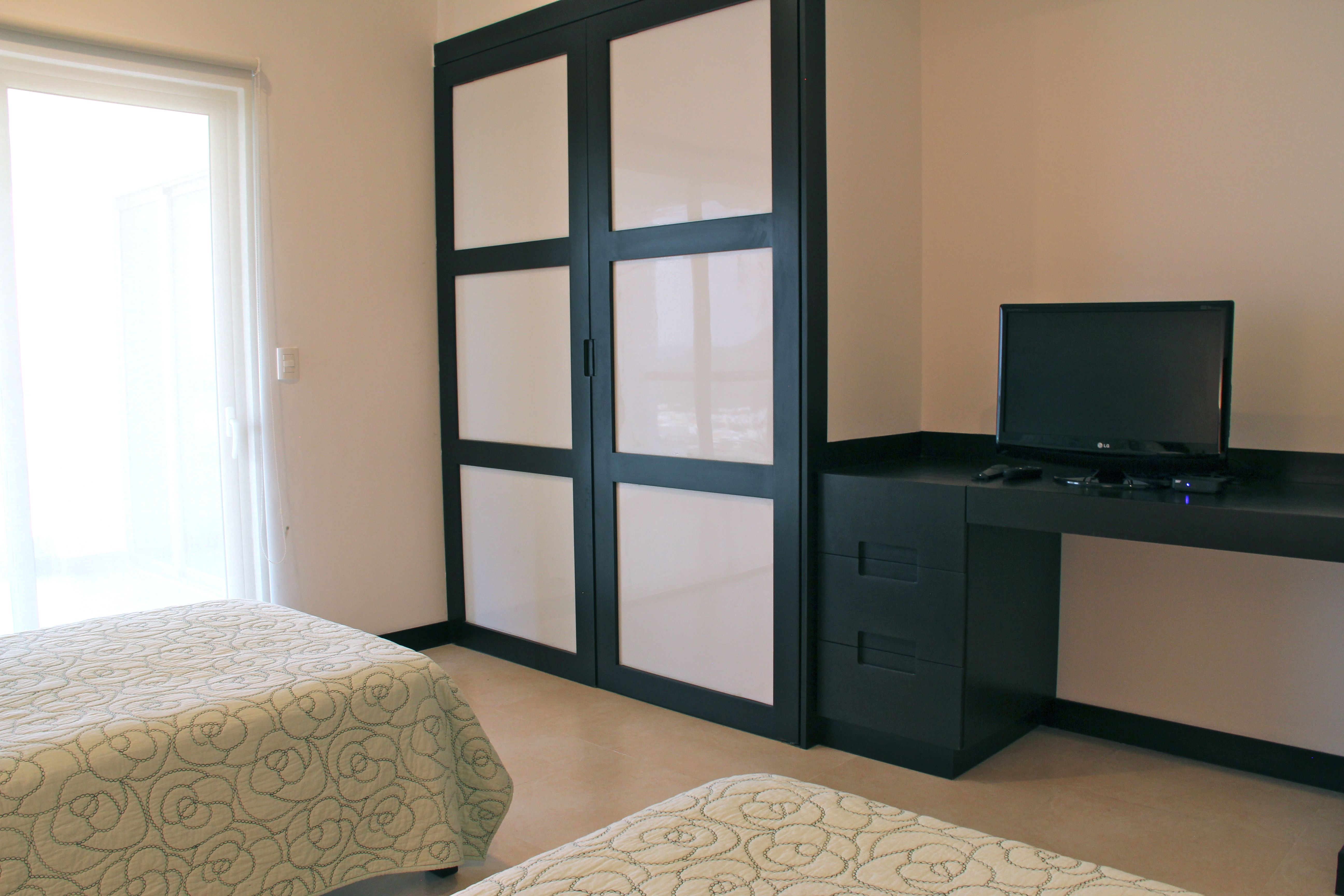 Closets and TV in second bedroom.