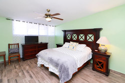 First bedroom with queen size bed and TV.