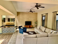 Living room with adjacent wet-bar, Smart TV and English programming.