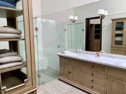 Master bathroom with custom furniture and large shower.