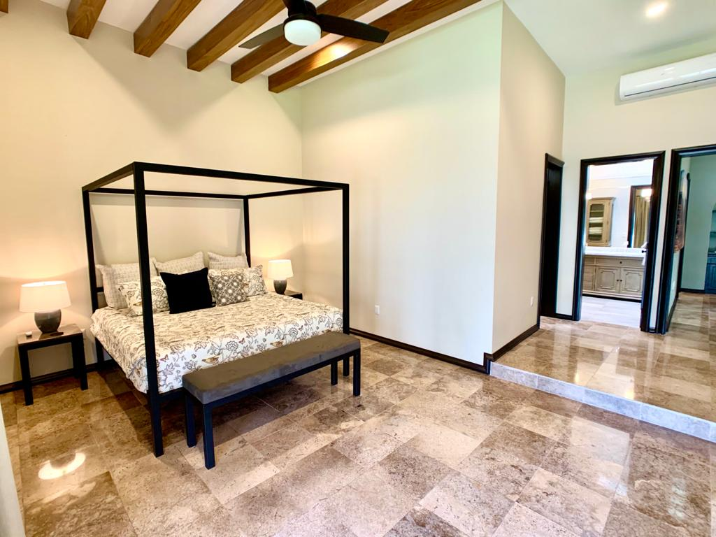 Master bedroom with custom bedframe and seating.