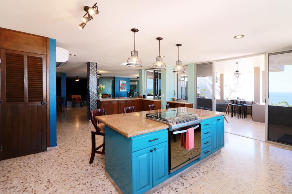 Large kitchen with island and access to terrace.