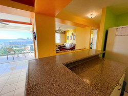 Open concept condo with large windows.