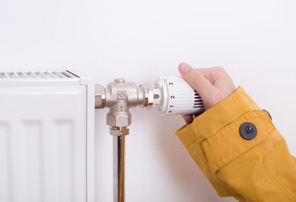 Ruka nastavující výkon radiátoru topení
