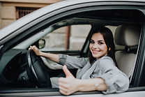 young-woman-sitting-car-showing-thumbs-u