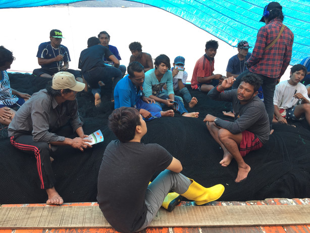 Outreach and Empowerment Team Leader Brendan Zarni Htun speak to migrant fishers for the FLIP Project