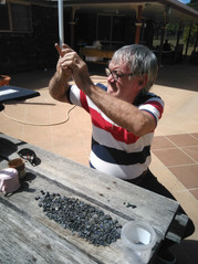 Rod inspecting some rough sapphire