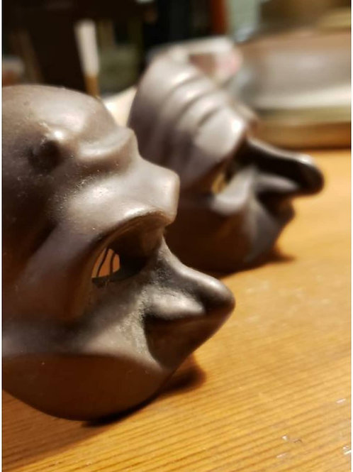 Pair of brass face masks wall hangings