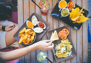 A variety of delicious-looking small plates with a woman dipping a chip into one of them