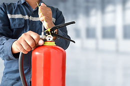 Inspector checking handle of fire extinguisher