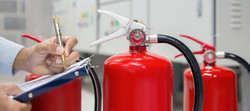 Inspector with clipboard checking fire extinguisher