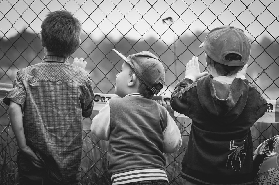 Three curious children peer through a fence