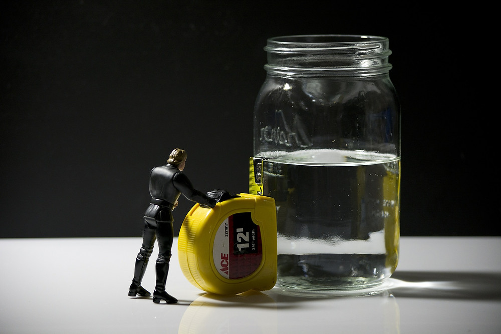 An action figure is holding up a measuring tape to see how full or empty glass is.