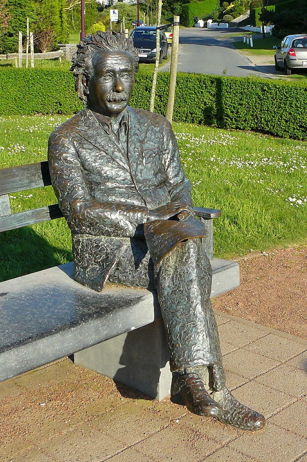 A statue of Albert Einstein is sitting on a bench reading.