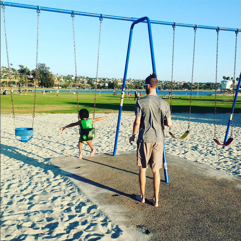 dad and son on swing at park