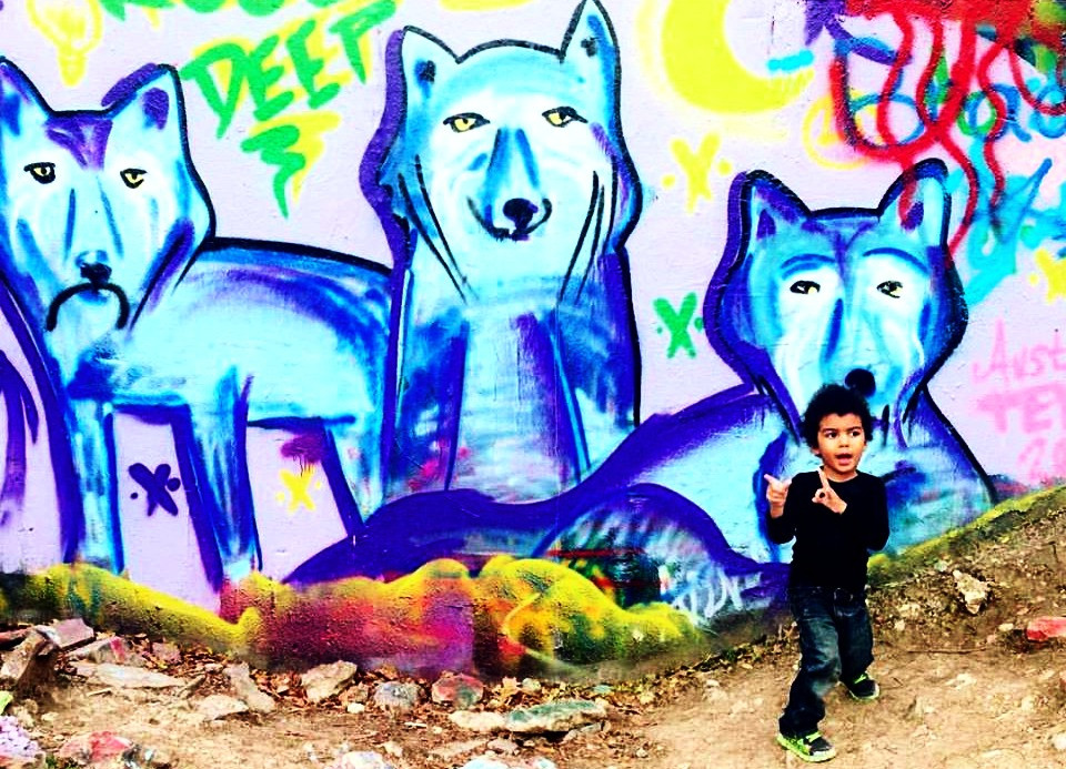 Jai in front of graffiti wall with wolves