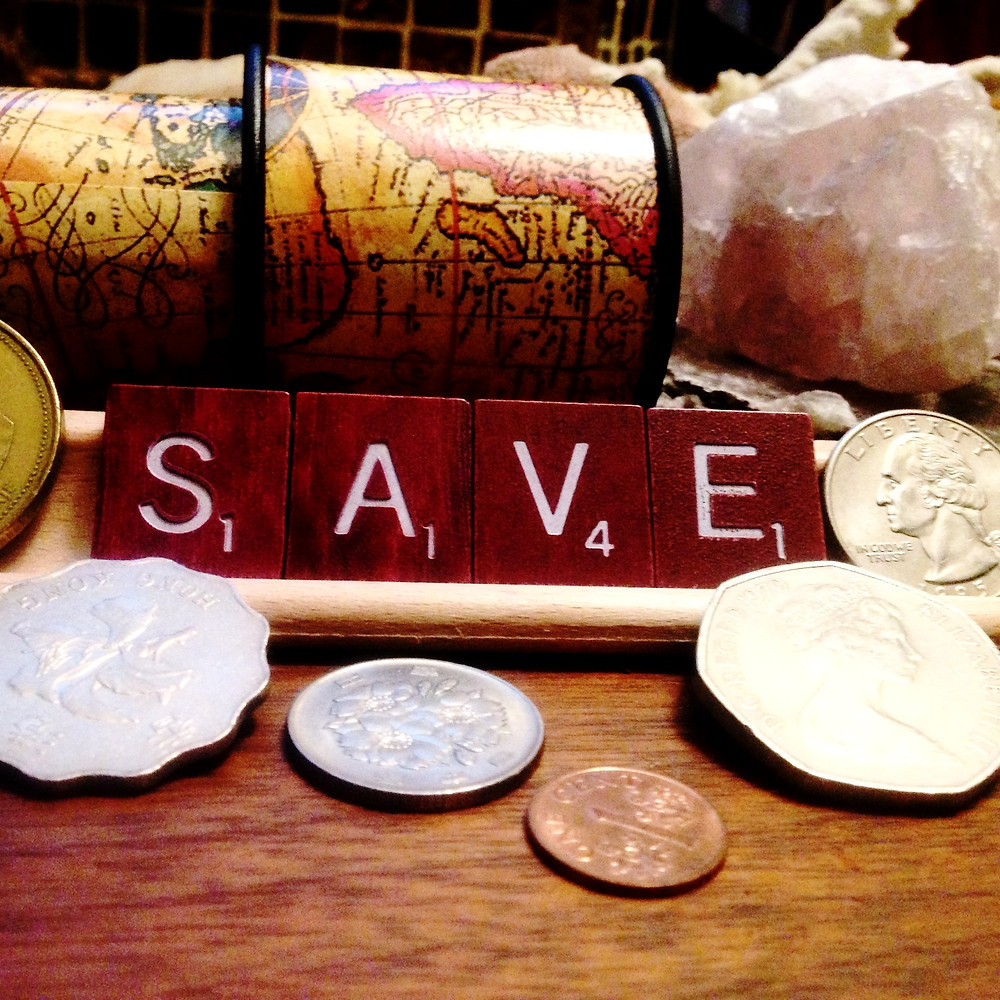 scrabble tiles spell save with coins surrounding