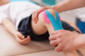 Masseur Physiotherapeut bei Krankengymnastik an getaptem Knie