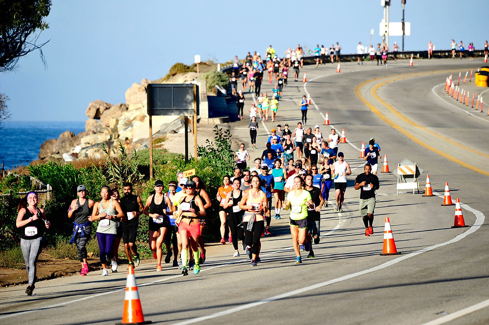 Runners running along the scenic Pacific Coast Highway at the Malibu Half Marathon