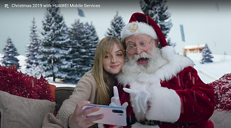 Santa and a young woman sit on a sofa taking a selfie together on the new Huawei iphone