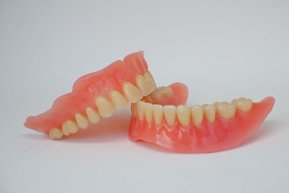 Close-up set of full denture; upper and lower removable denture with pink plastic gum,anterior and p