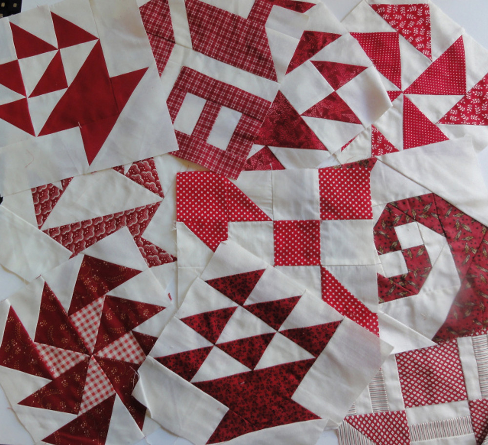 """Ten 8"""" finished red and white pieced blocks."""