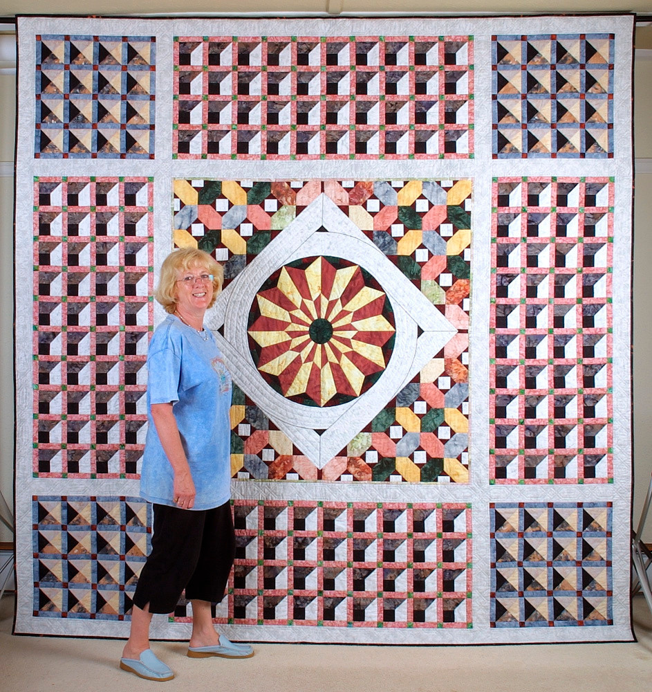 """Chris with her quilt Venetian Celebration (104"""" x 104""""), inspired by the floor tiles of St. Mark's Cathedral in Venice"""