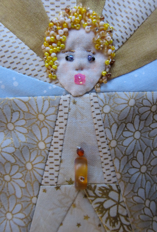 Detail view of angel face:  pink flower sequin for mouth, beads for eyes and hair, hand-stitched face details.