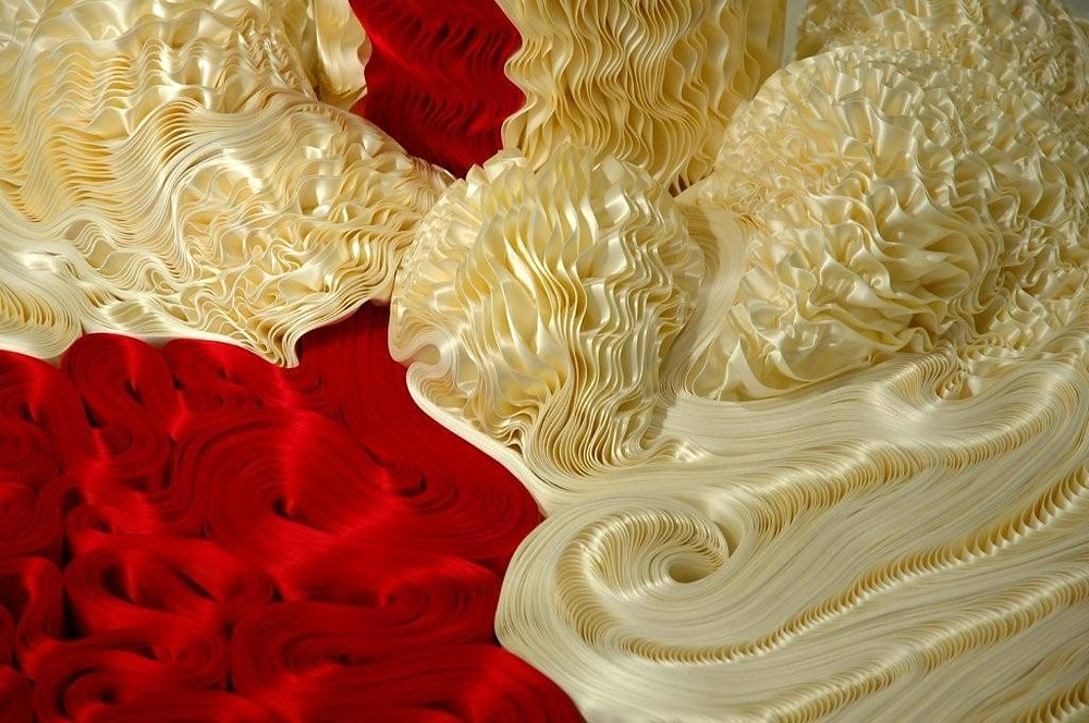 Close-up view of the hand-folded and pressed pleats, and sculpted into undulating liquid-like shapes.