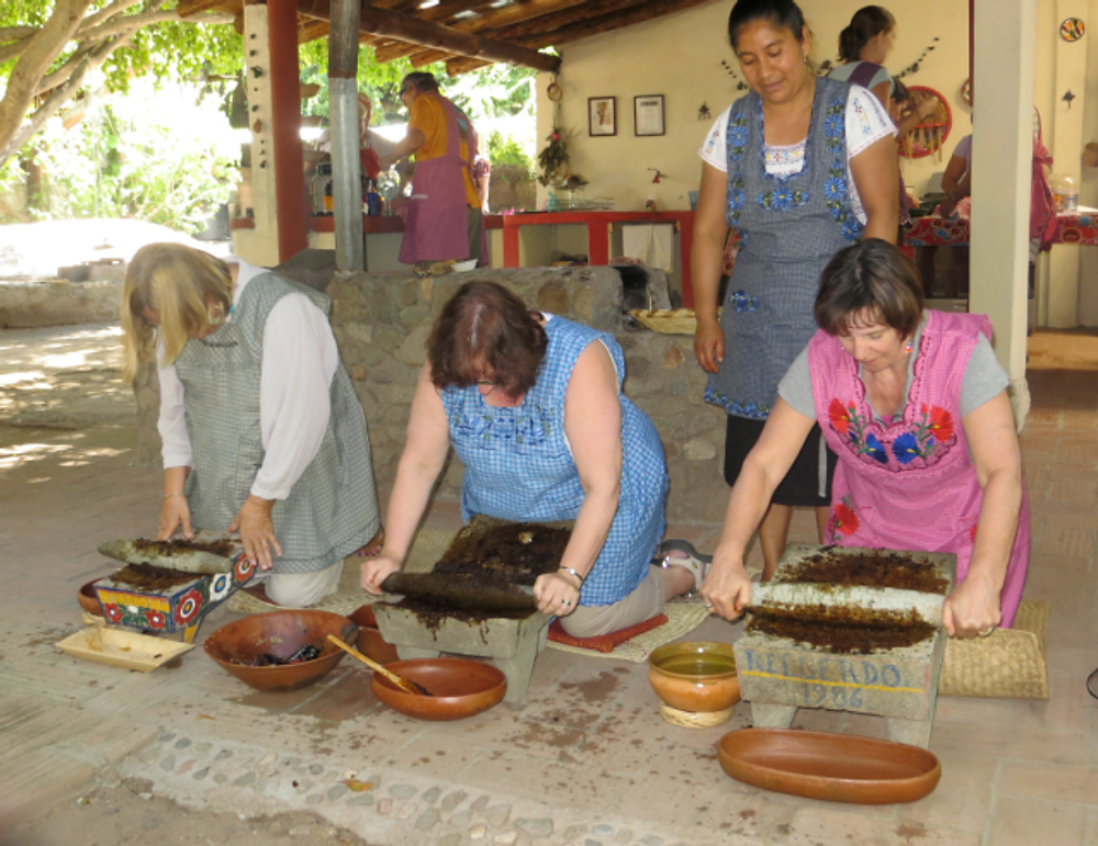 Grinding mole ingredients  at a traditional outdoor cooking school.