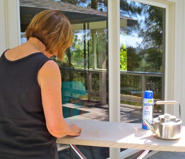 """One of our """"innovations"""" in recent years has been to move the ironing station outside to the deck for the cool breezes and lovely views. If you look closely, you can see Joen at her laptop, reviewing quilts for her upcoming book."""