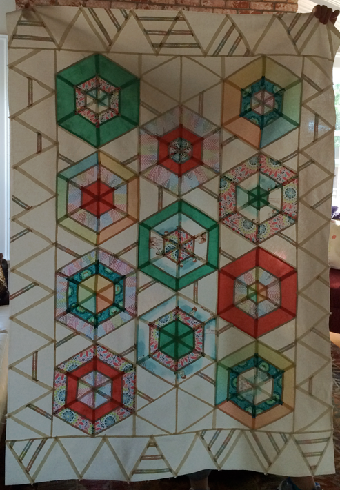 Stained glass view:  back lit finished quilt top.  The insets of the setting triangles illuminated.