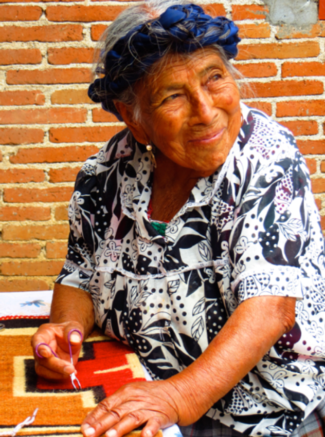 Oaxacan artisan trimming  loose threads on woven rug.