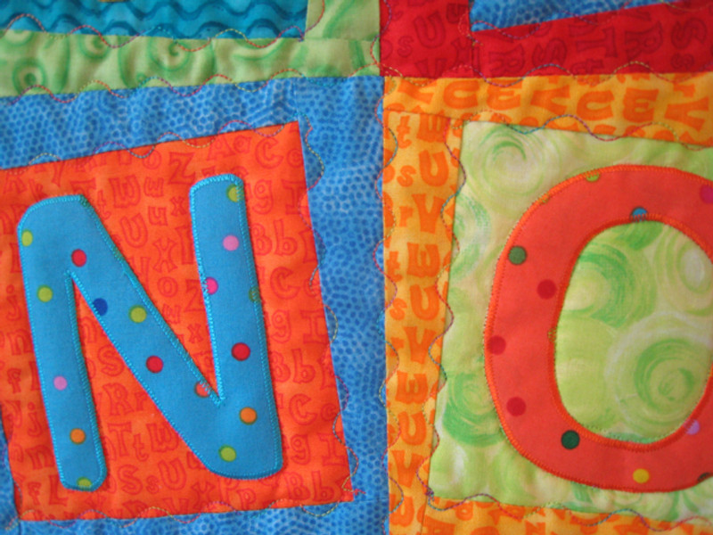 Detail of Alphabet Soup, made by Chris Porter; Chris adapted one of her machine's embroidery stitches to quilt the wiggly pattern around each block.