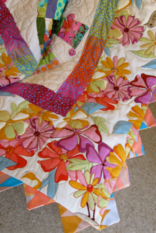 Detail view of quilt back with faced binding and prairie points.