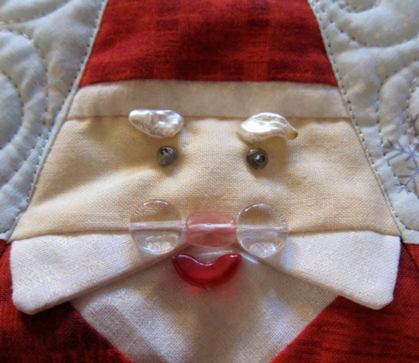Detail from Santa Smiles Tree Skirt--face details are German glass beads and seed pearls.