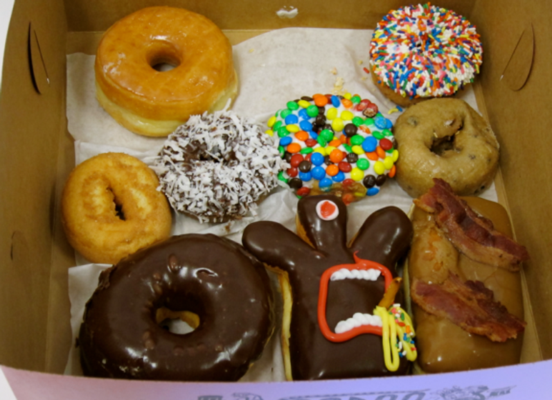 I traversed Portland's TSA security lines, braved the overhead compartment crush, and suffered plaintive pleas for tastes from passersby in order to deliver these startlingly delicious doughnuts to my office.  Gotta say:  Voodoo doughnuts are worth the effort!  (Don't you just love that oddball Voodoo doll?)