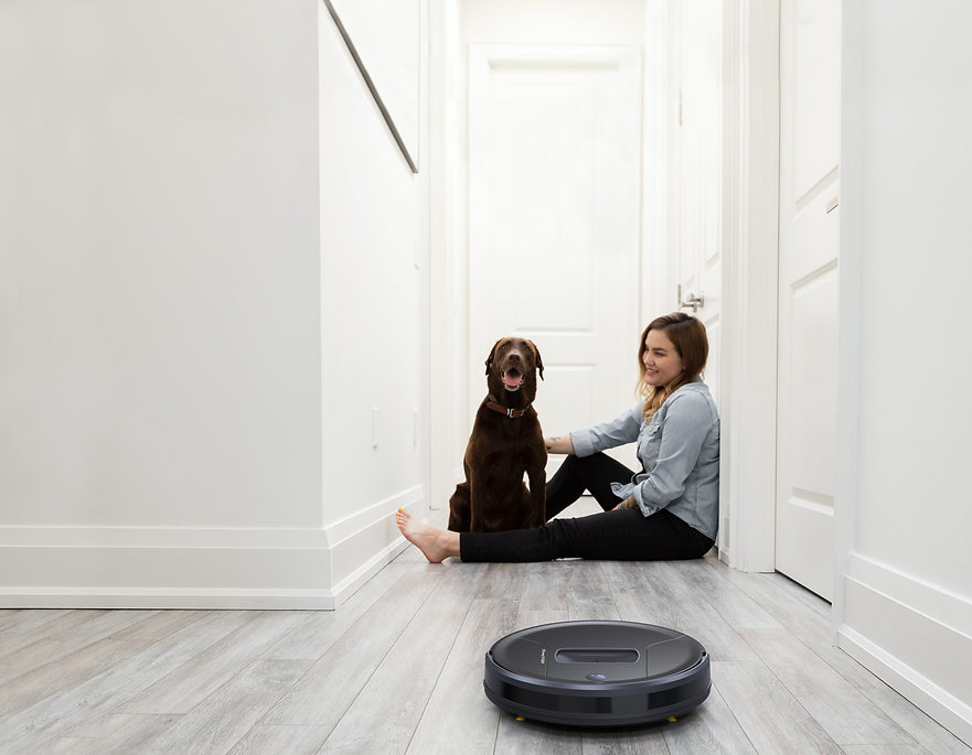 Girl with dog smiling in hallway while Bob PetHair Vision vacuums
