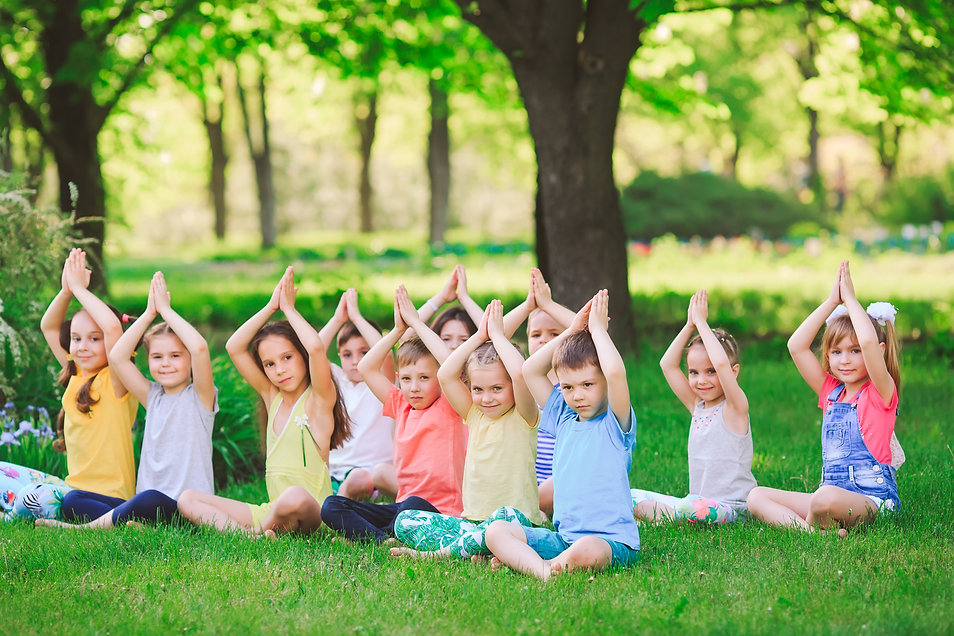 A large group of children engaged in yog