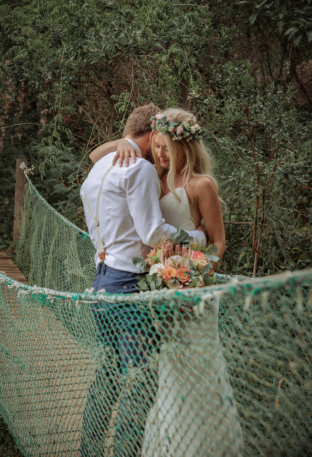 Bride and groom embracing on a string bridge during their wedding in Portugal