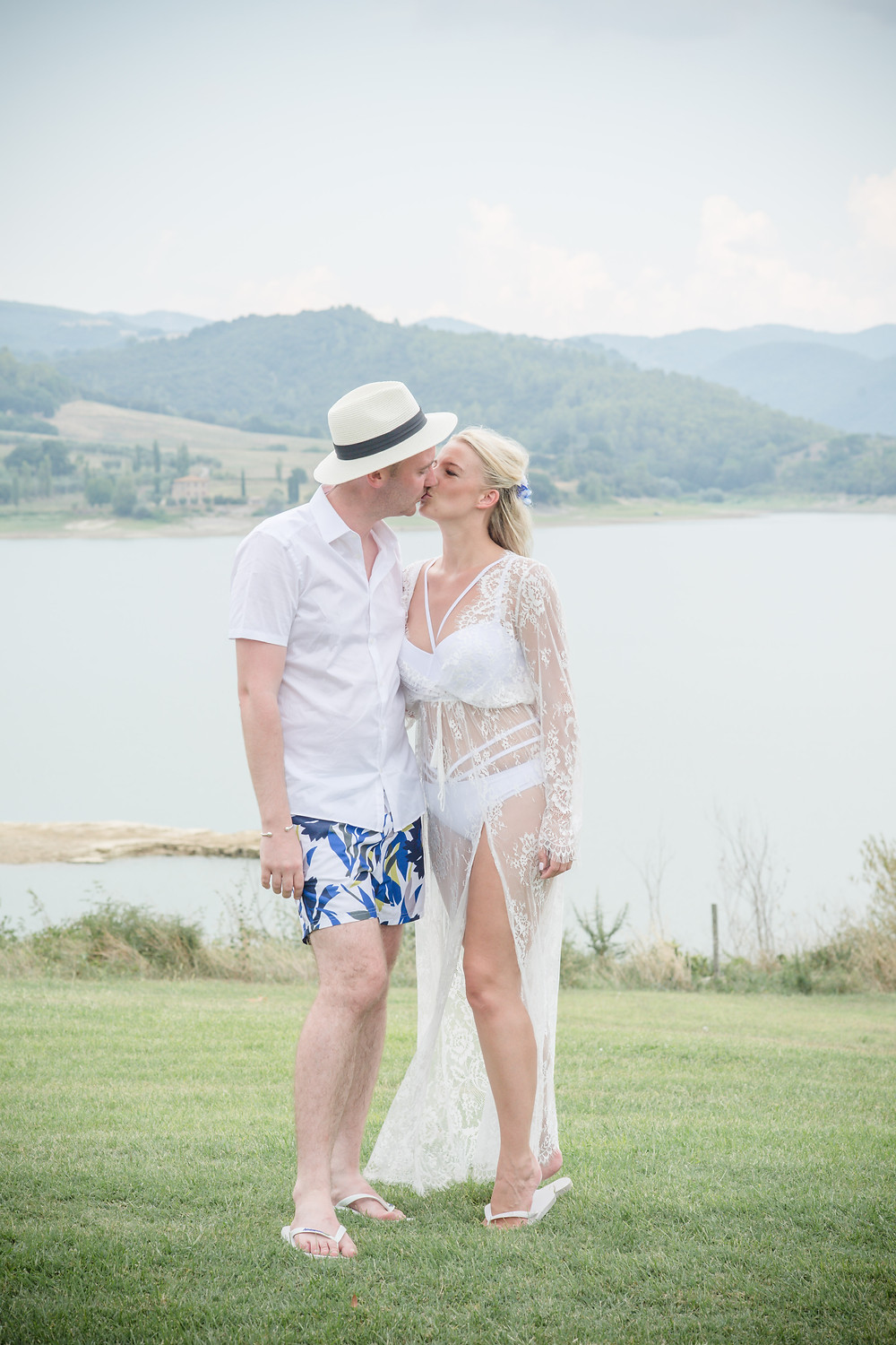 Bride and groom kissing in swimsuits in front of a lake and rolling mountains