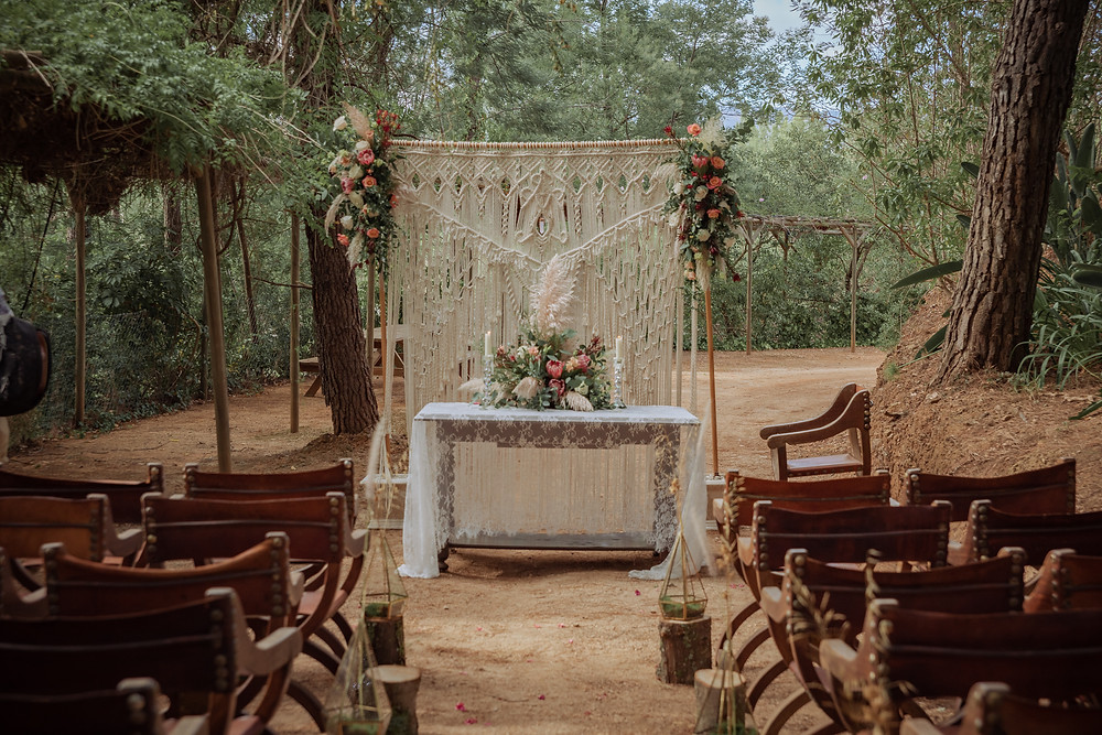 Wedding ceremony with a macrame curtain and protea flowers