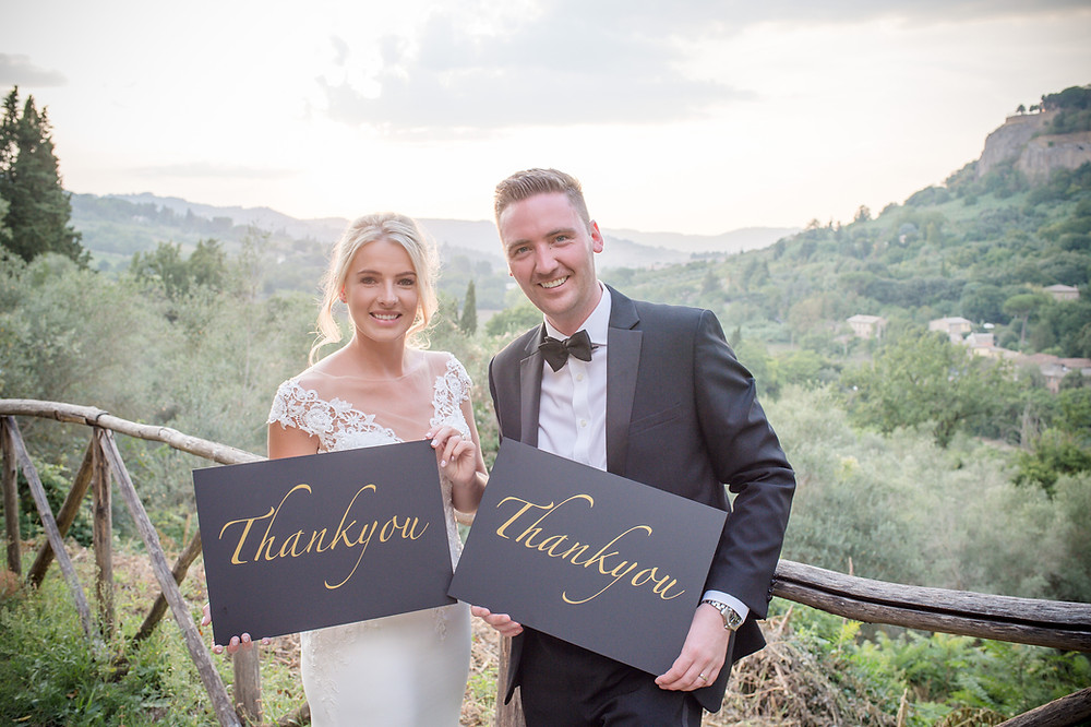 Bride and groom holding wedding thank you cards with mountains in the background