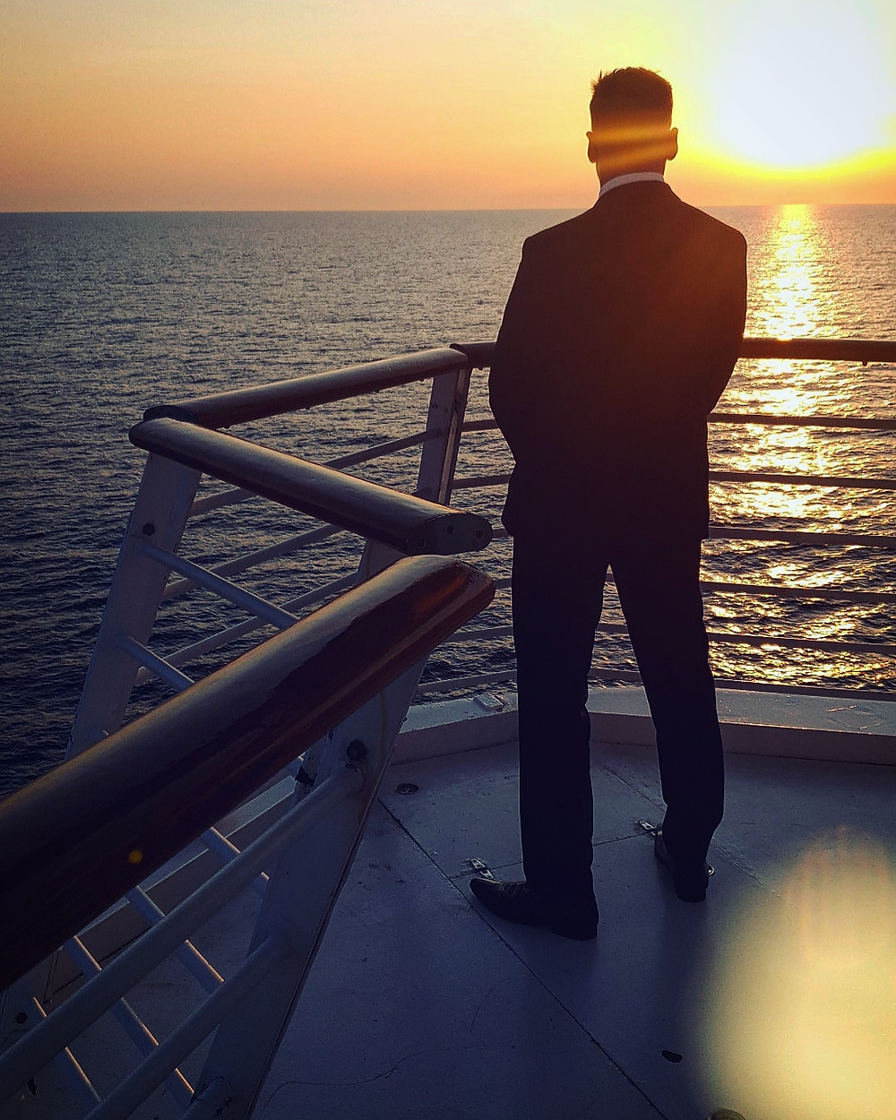 man-standing-on-a-cruise-ship-watching-the-sunset