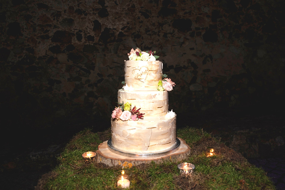 Wedding cake with a silver birch effect sitting on a tale of moss surrounded by candles, in Portugal